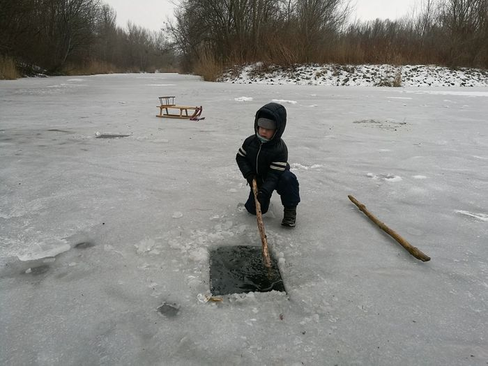 Boy Holding Stick In Water While Kneeling On Ice Field During Winter