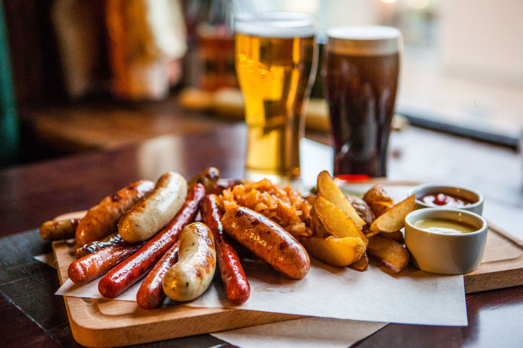 Close-up of sausages and french fries served with beers on table