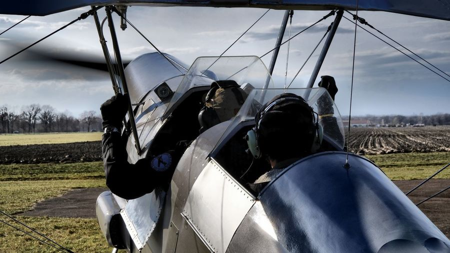 Rear view of men sitting in airplane on field