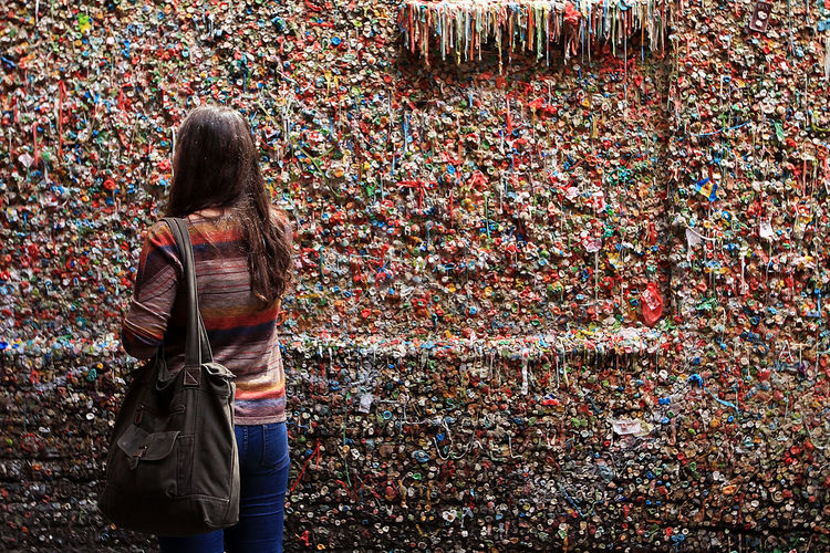 Rear view of young woman standing against gum wall