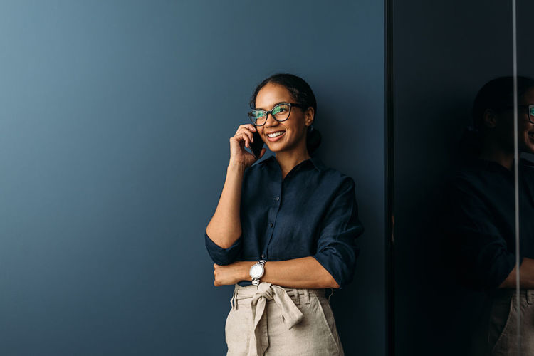 Businesswoman talking on phone while standing in office
