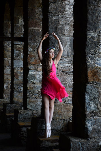 Beautiful ballet dancer posing against old column