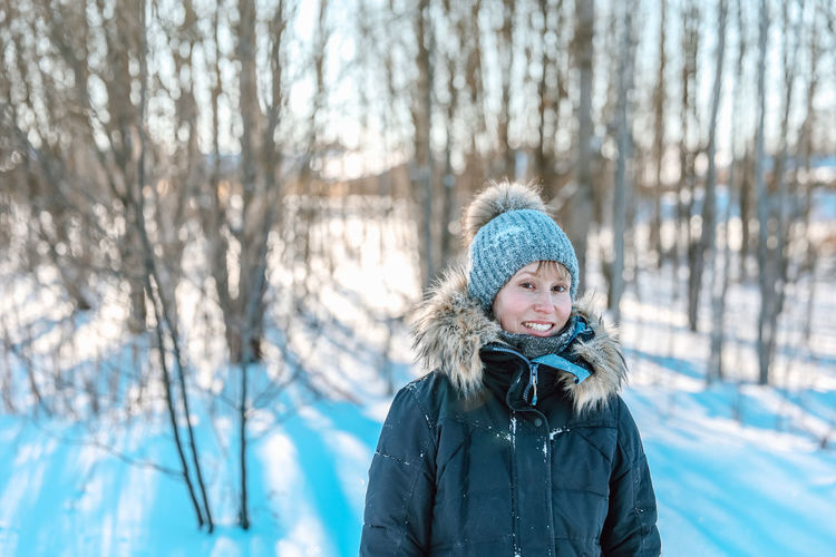 Portrait of woman in snow against trees during winter