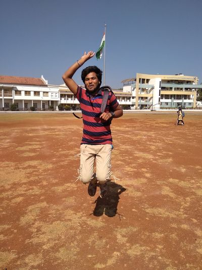 Portrait of young man jumping on land against built structure