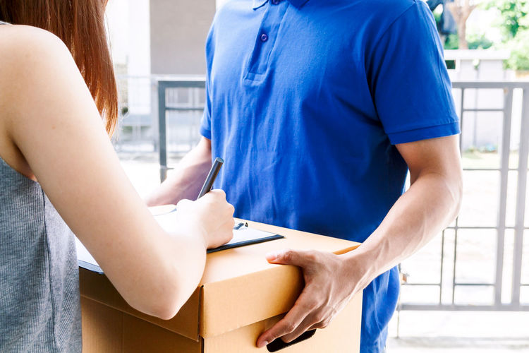 Woman putting signature in clipboard on cardboard box with delivery man Delivery Adult Beginnings Blue Box Care Casual Clothing Connection Focus On Foreground Holding Indoors  Lifestyles Men Midsection People Real People Standing Technology Two People Women Young Adult Young Women