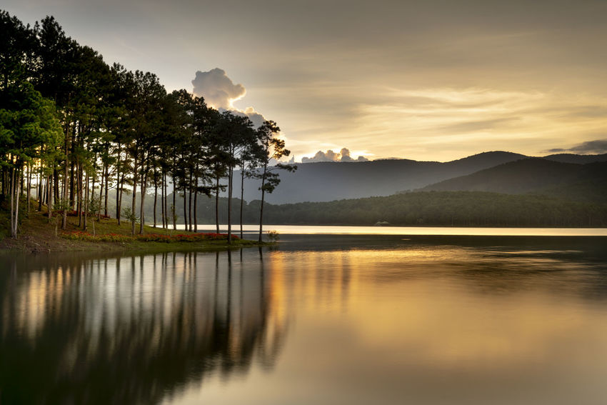 The peaceful time when the sun sets. Colorful fantastic clouds and mountain and pine forest make a silhouette reflecting in the lake. Summer is coming. Reflection Beauty In Nature Sky Scenics - Nature Tranquil Scene Tranquility Water Outdoors Waterfront Non-urban Scene Nature No People Idyllic Mountain Lake Sunset Pine Forests Lonely Concept Amazing Backgrounds Sunrise Reflecting Rural Scene Silhouette