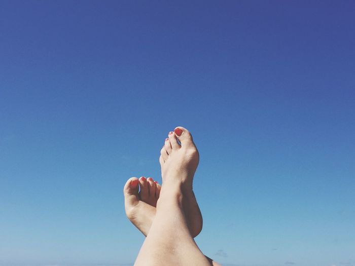 Low section of woman with feet up against blue sky