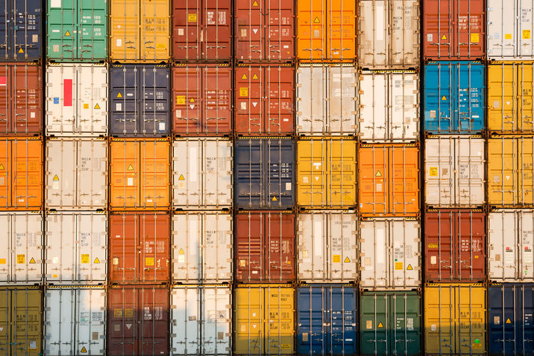 frontal view of a Stack of containers Backgrounds Business Cargo Container Commercial Dock Container Distribution Warehouse Freight Transportation Harbor Industry Large Group Of Objects Pier Shipping  Stack Trading Transportation Warehouse
