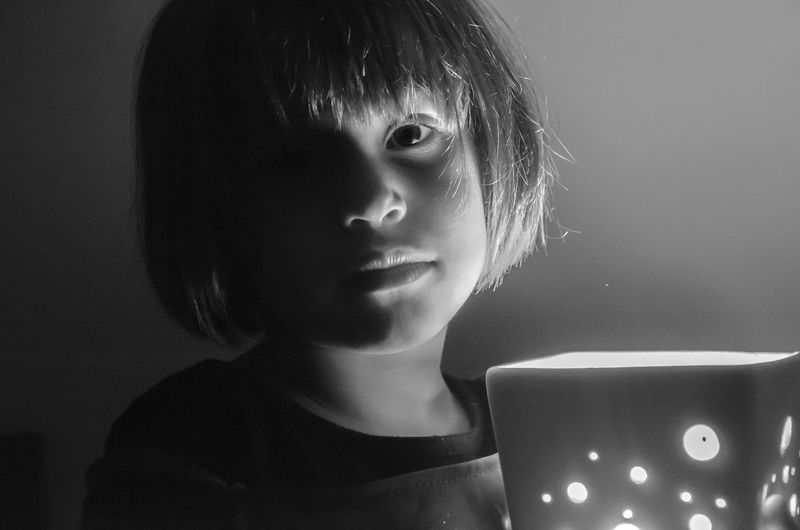 Close-Up Portrait Of Girl Standing By Illuminated Lamp Shade Against Wall