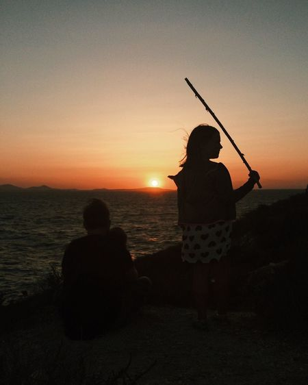 Rear view of two men sitting on shore against sunset