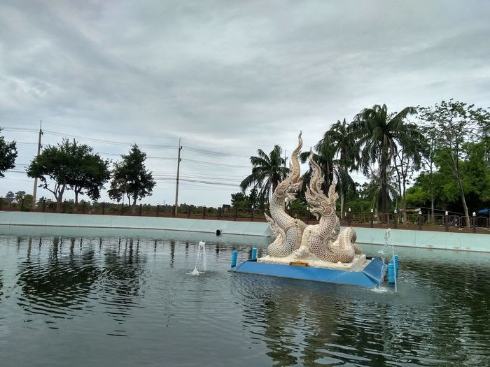 Statue by swimming pool against sky