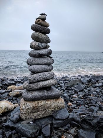 Stack of Stones balanced by seaside Stack Sea Rock - Object Water Beach Pebble Stone - Object Cloud - Sky Stones Balancing Pebbles No People Outdoors Horizon Over Water Vertical Scenics Beauty In Nature Stack Sea Rock - Object Sunlight Water Beach Pebble Vertical