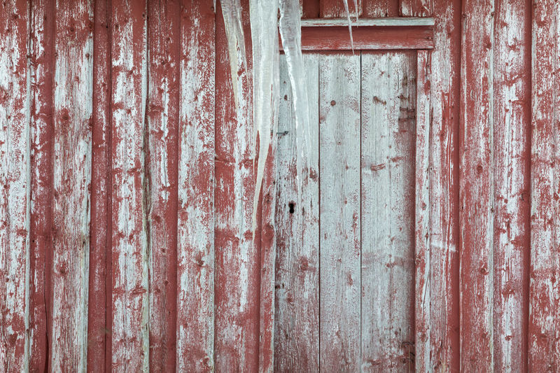 Close-up of door from an old barn with icicles hanging in front of the door and red paint peeling off the wooden panels Red Wood - Material Wood Paneling Deterioration Bad Condition Barn Peeling Off Weathered Paint Arctic Cold Temperature Winter Icicle Door Textured  Pattern Backgrounds Full Frame Old Built Structure No People Wall - Building Feature Architecture Damaged Run-down Building Exterior Decline Close-up Day Wood Wood Grain Dirty