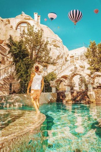 Cave Cave Hotel Hotel Boy Man Hot Air Balloons Kapadokya Cappadocia Cappadocia/Turkey Swimming Pool EyeEm Selects Hot Air Balloon Water Young Women Full Length Tree Standing Motion Sky Luxury Hotel Infinity Pool Tourist Resort Hotel Suite Poolside Rock Formation Swimming Lane Marker Resort