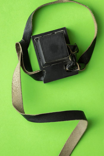 High angle view of eyeglasses on table against green background