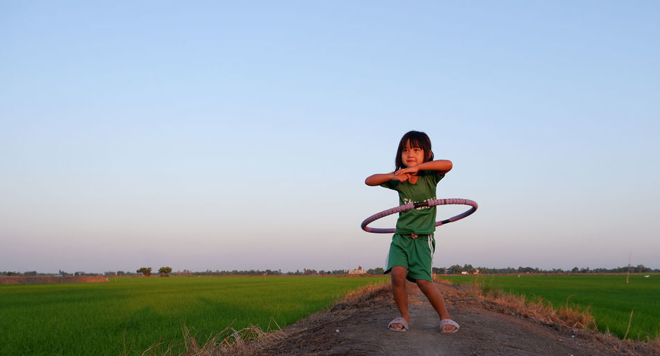 Full length of girl playing with plastic hoop amidst landscape