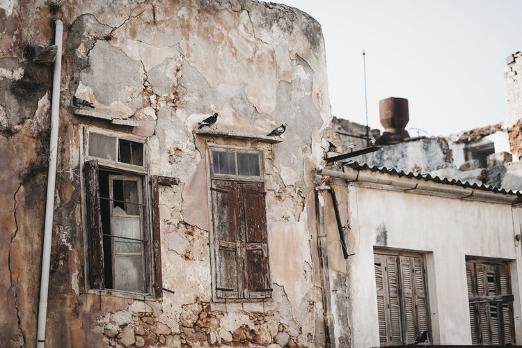 Abandoned Architecture Building Building Exterior Built Structure Damaged Day Deterioration History House Low Angle View No People Obsolete Old Outdoors Residential District Ruined Sky Stone Wall The Past Wall - Building Feature Weathered Window