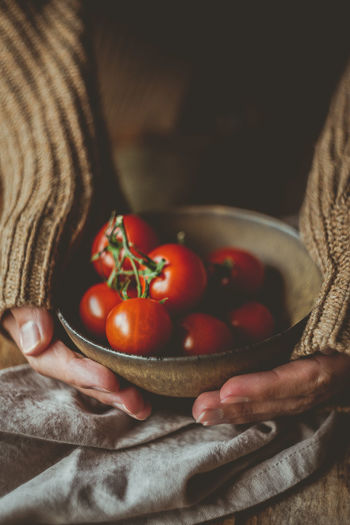 Cropped hands of woman holding bowl with cherry tomatoes on table
