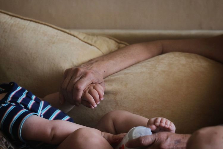 Cropped image of father holding hands with baby on sofa at home