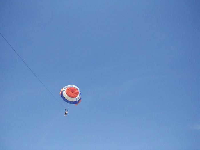 Low angle view of person parasailing against blue sky