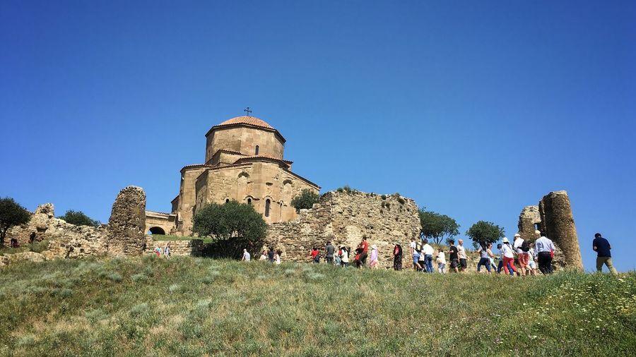 People outside jvari monastery on hill against clear blue sky