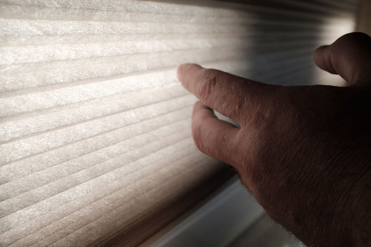 Close-Up Of Man Hand By Blinds At Home