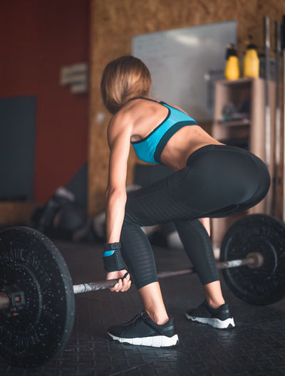 Body Conscious Dumbbell Exercise Equipment Exercising Full Length Gym Healthy Lifestyle Indoors  Leisure Activity Lifestyles Muscular Build One Person Physical Activity Real People Sport Sports Clothing Sports Training Standing Strength Strength Training Tire Wellbeing Women Young Adult Young Women
