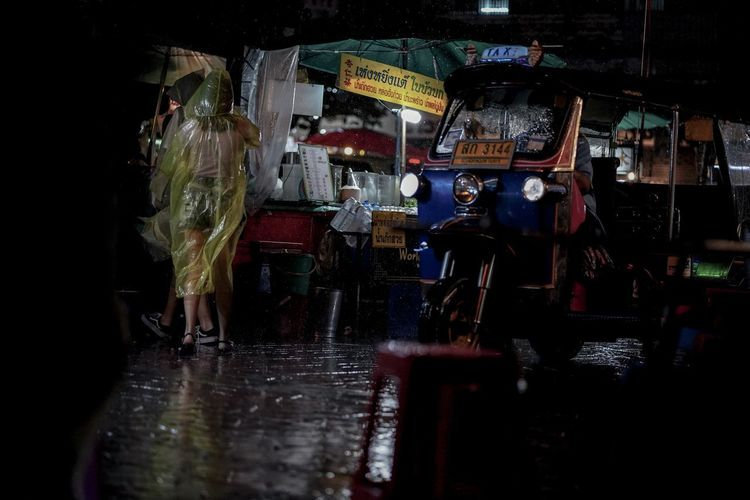 People on wet street in city at night during monsoon