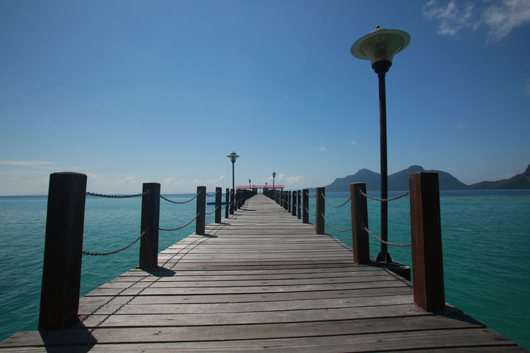Wooden pier on sea against clear blue sky