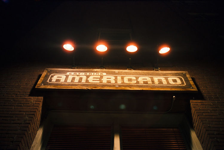 Low angle view of illuminated information sign at night