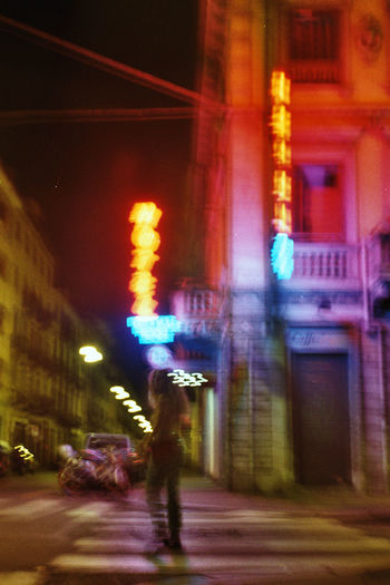 Blurred motion of person walking on illuminated street at night