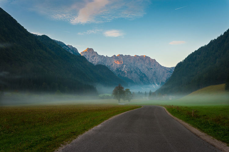 Empty Road On Field Leading Towards Mountains Against Sky During Foggy Weather