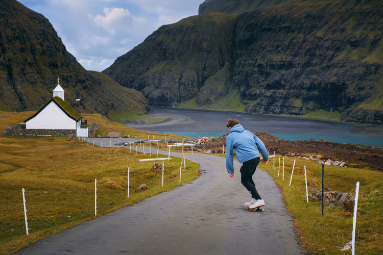 Rear view of man walking on road against mountains