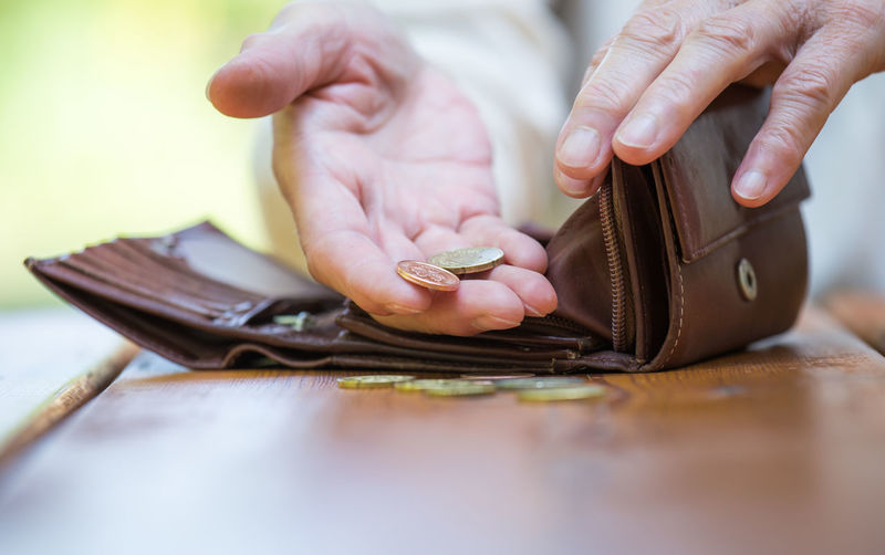 Close-up of woman hand counting coins from wallet on table