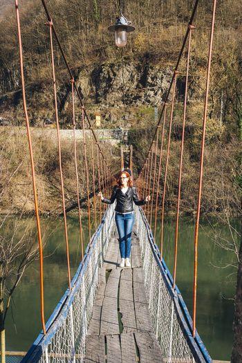 Woman standing on footbridge over river