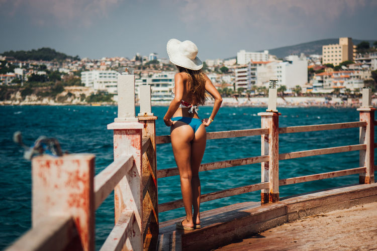 Woman in bikini standing on bridge while looking at sea