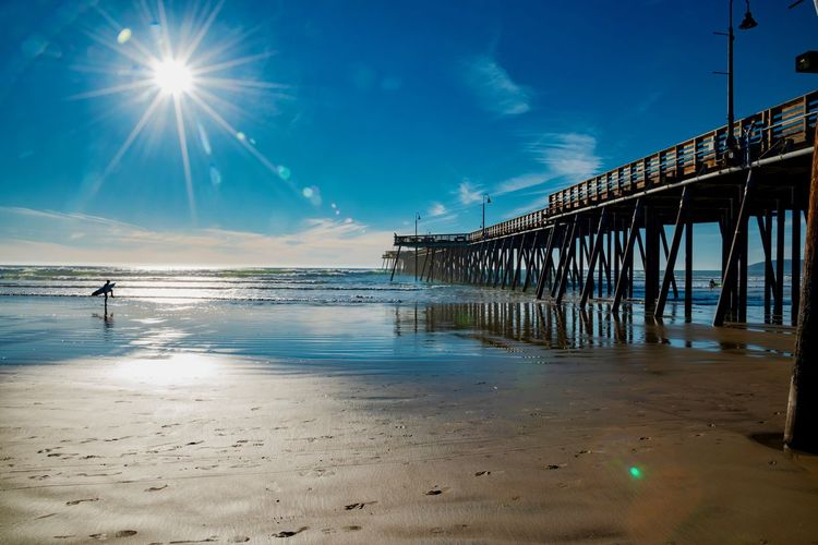 Water Sky Beach Built Structure Land Sea Nature Architecture Sunlight Pier Reflection Beauty In Nature Scenics - Nature Sun Sand Tranquil Scene Incidental People Lens Flare Tranquility Outdoors Architectural Column