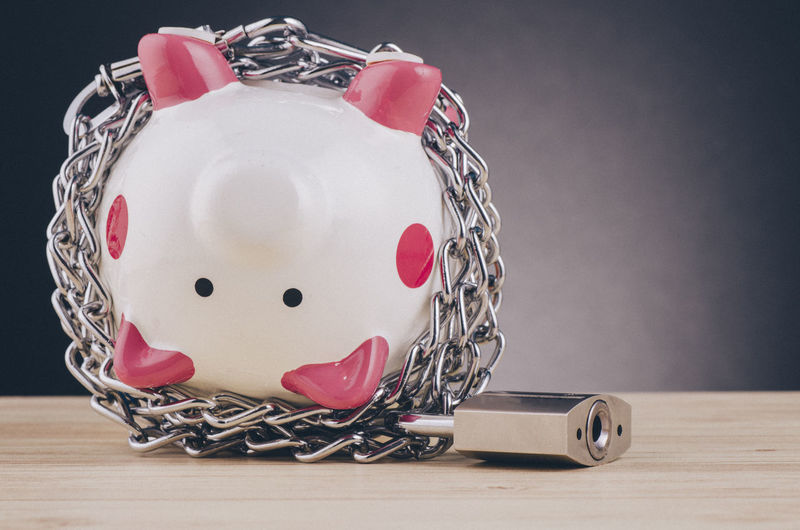 piggy bank surrounded by chains and padlock on wooden desk Still Life Table Indoors  Close-up No People Representation Piggy Bank Wood - Material Heart Shape Studio Shot Pink Color Human Representation Creativity Chain Investment Art And Craft Savings Focus On Foreground Toy Personal Accessory