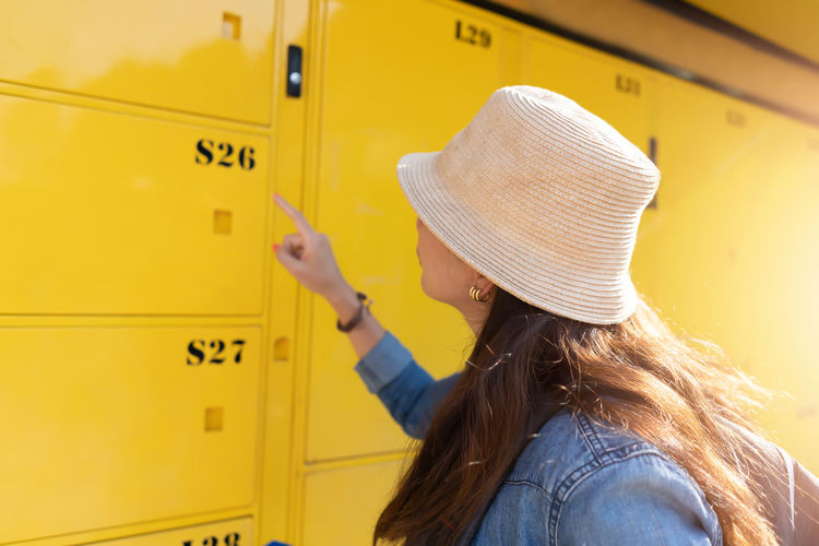 Woman traveler using the locker service and go vacation in the city. Travel concept Yellow Real People Hat One Person Women Lifestyles Leisure Activity Clothing Adult Headshot Casual Clothing Communication Portrait Hairstyle Western Script Text Rear View Long Hair Females Outdoors Locker Industry Technology Travel Traveling Backpack
