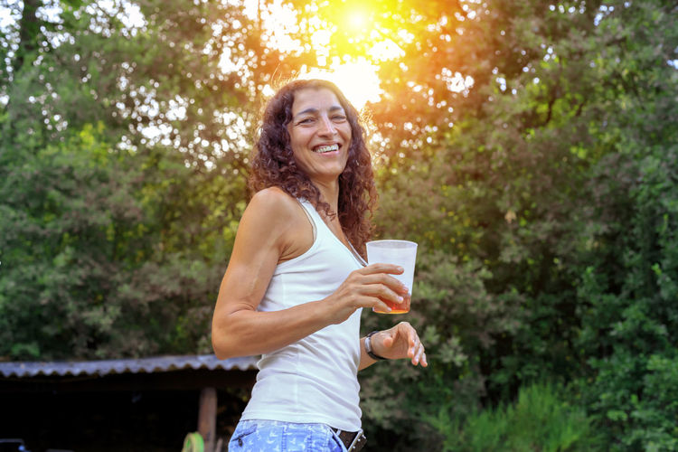 Portrait Of Smiling Woman Having Drink Against Trees