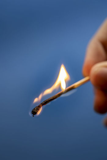 Close-up of hand holding burning candle