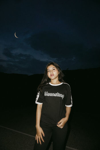 Young woman standing against sky at night