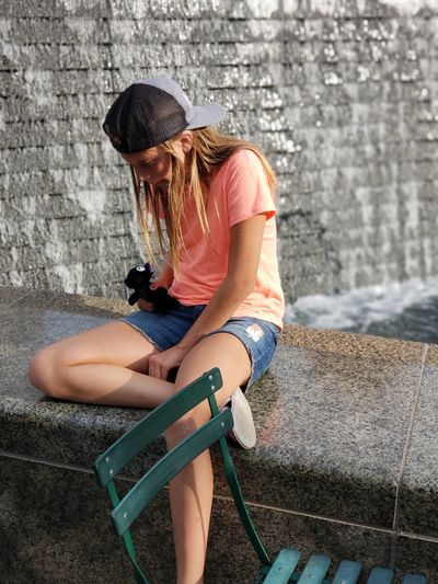 One Person No Filter Fountain Girl Hat Fountains Detroit EyeEm Selects Young Women Sitting Full Length Looking Down Limb Casual Clothing Joint - Body Part Human Knee Knee
