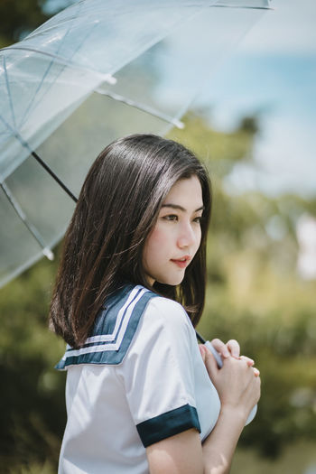 Young woman with umbrella standing against sky
