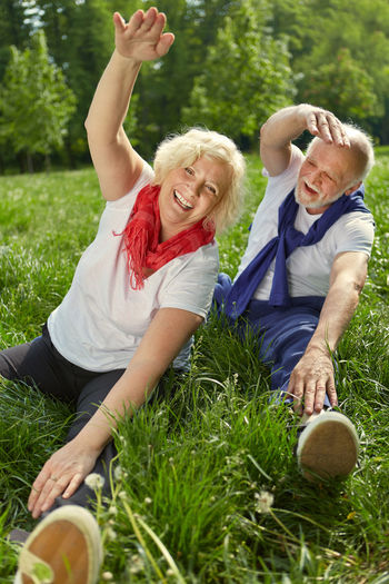 Smiling Couple Doing Yoga On Grassy Field