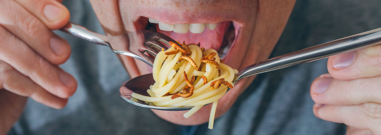 Midsection of man eating noodles and worms in restaurant