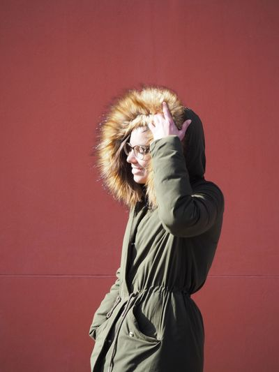Side view of happy young woman wearing fur coat against red wall