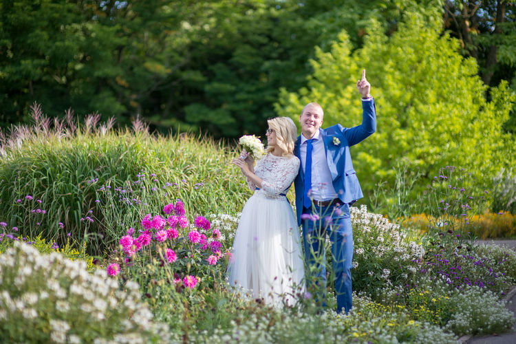 Groom gesturing while bride holding bouquet while standing amidst plants at park