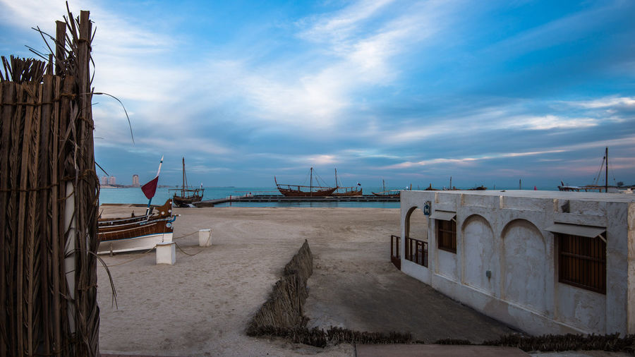 Qatara Traditional Dhow Festival Doha Qatar Sky Cloud - Sky Architecture Nature Built Structure Water Sea Transportation Land Nautical Vessel Beach Mode Of Transportation No People Day Beauty In Nature Outdoors Scenics - Nature Building Exterior Horizon Over Water Doha Katara Cultural Village