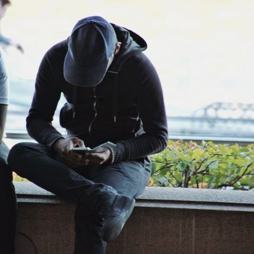 Young man using a mobile device Young Adult Male Technology Everywhere Mobile Love Technology Mobile Phone Close Up Street Photography Street Photography People Photography Street City Life Colour Of Life Urban Lifestyle Streetphotography Australia Casual Clothing Sitting Faceless Hat Internet Addiction People And Places Mobile Conversations Welcome To Black TCPM
